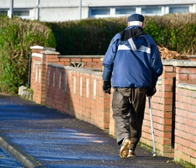 Elderly man walking with stick